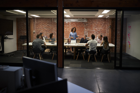 Business Team Having Late Night Meeting Sitting Around Boardroom Table