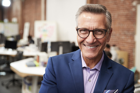 Portrait Of Mature Businessman In Modern Open Plan Office With Business Team Working In Background