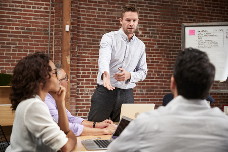 Young Businessman Standing And Leading Office Meeting Around Table Stock Photo