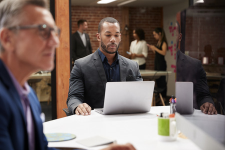 Businessman Working At Desk On Laptop In Open Plan Office With Colleagues In Background Stock Photo