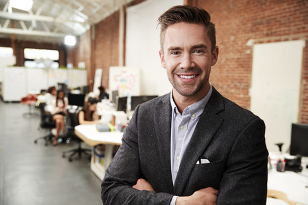 Portrait Of Businessman In Modern Open Plan Office With Business Team Working In Background