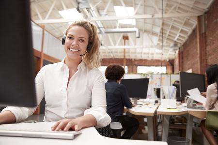 Portret van vrouwelijke klantenservicemedewerker die aan de balie in het callcenter werkt Stockfoto