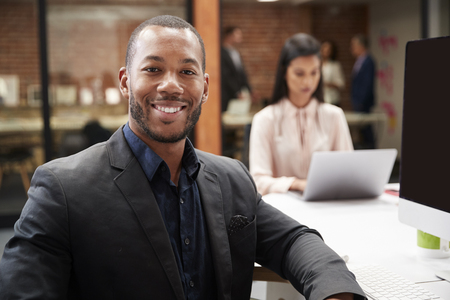 Portrait Of Businessman Working At Desk On Computer In Open Plan Office With Colleagues In Background Stock Photo