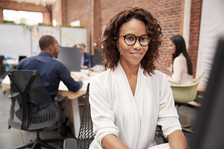 Female Customer Services Agent Working At Desk In Call Center Stock Photo