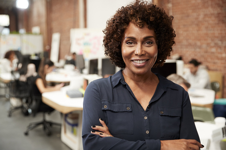 Portrait Of Mature Businesswoman In Open Plan Office With Business Team Working In Background