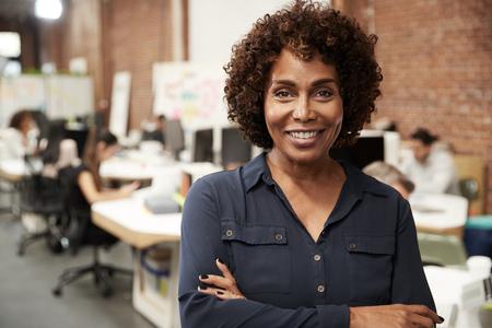 Portret van een volwassen zakenvrouw in een open kantoor met een zakelijk team dat op de achtergrond werkt