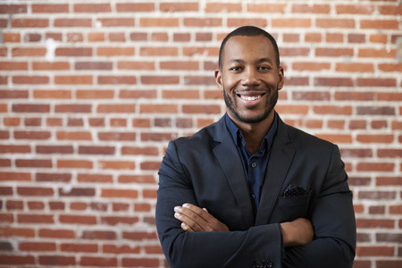 Portrait Of Businessman Standing Against Brick Wall In Modern Office Stock Photo