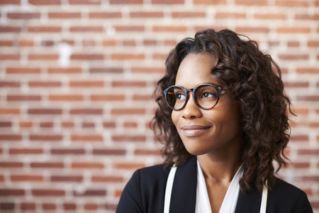 Smiling Businesswoman Wearing Glasses Standing Against Brick Wall In Modern Office Stock Photo