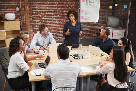 Mature Businesswoman Standing And Leading Office Meeting Around Table