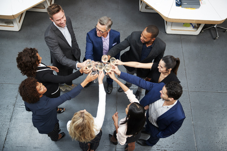 Overhead Shot Of Business Team Celebrating Success With Champagne Toast In Modern Office