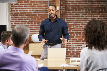 Businessman Standing And Leading Office Meeting Around Table Stock Photo