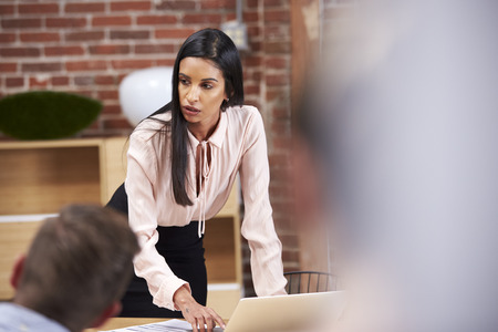 Young Businesswoman Standing And Leading Office Meeting Around Table