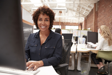 Portrait Of Female Customer Services Agent Working At Desk In Call Center