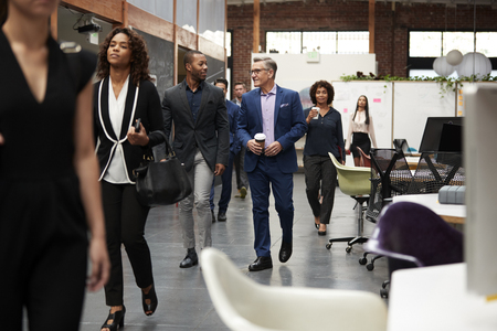 Businesspeople Arriving For Work In Busy Modern Open Plan Office Stock Photo