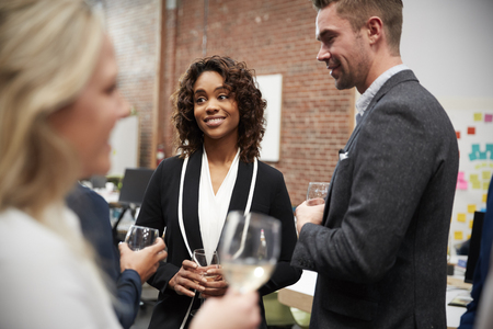 Business Team Socializing At After Works Drinks In Modern Office