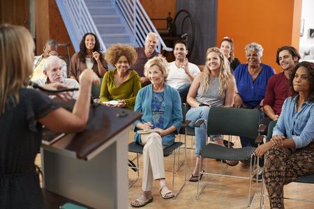 Groupe participant à la réunion de quartier à l'écoute de l'orateur dans un centre communautaire