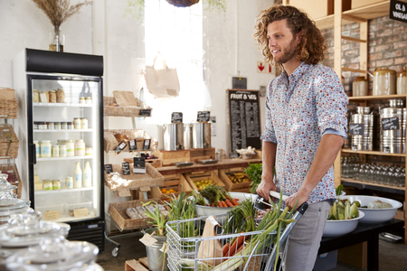 Young Man Buying Fresh Fruit And Vegetables In Sustainable Plastic Free Grocery Store Stock Photo