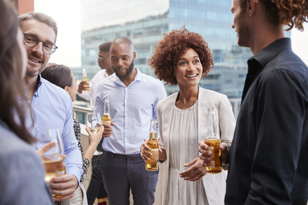 Office colleagues socialising with drinks in the city after work Stok Fotoğraf