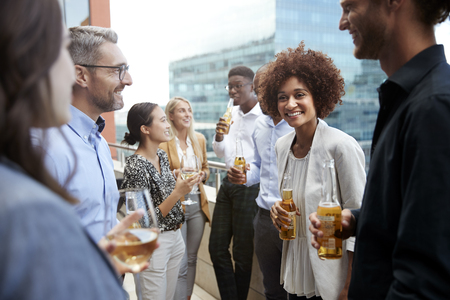 Business colleagues talking and drinking together on a balcony in the city after work