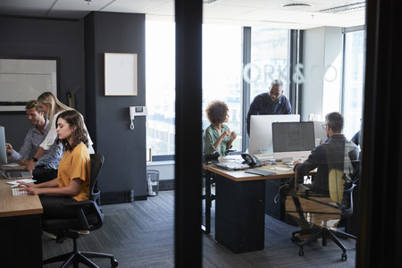 Young creative team working together at computers in a casual office, seen through glass wall Stock Photo