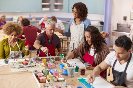 Group Of Mature Adults Attending Art Class In Community Centre With Teacher