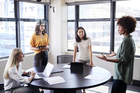 Vrouwelijke creatievelingen in een vergaderruimte luisteren naar hun collega die een informele presentatie geeft