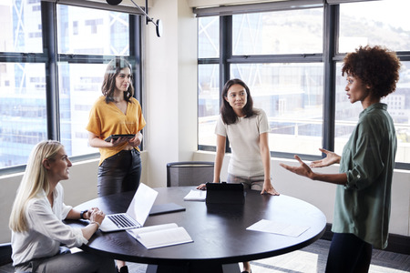 Weibliche Kreative in einem Besprechungsraum, die ihrer Kollegin bei einer informellen Präsentation zuhören