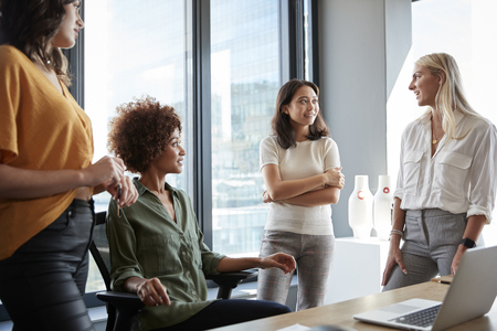Four female colleagues in discussion at a desk in a creative office, three quarter length, close up Imagens