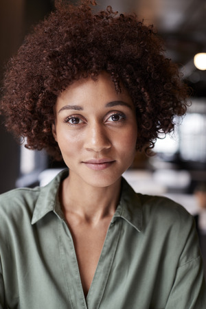 Close up portrait of millennial black female creative in an office smiling slightly to camera
