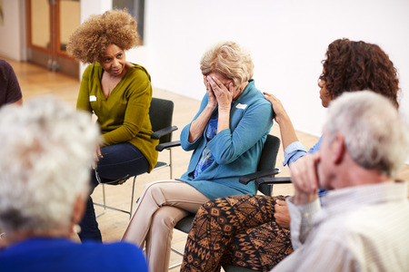 Unhappy Woman Attending Self Help Therapy Group Meeting In Community Center