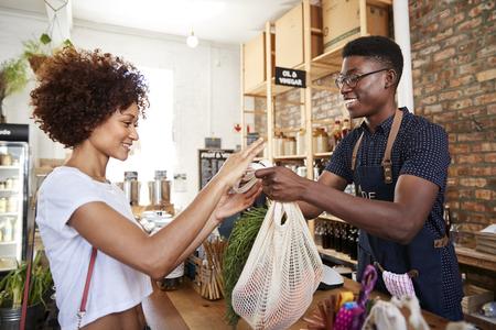 Cliente que paga por comprar en la caja de la tienda de comestibles sin plástico sostenible