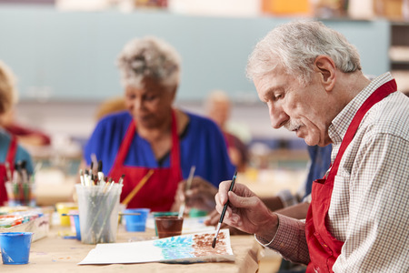 Retired Senior Man Attending Art Class In Community Centre 免版税图像