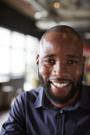 Mid adult black male creative sitting in an office social area, head and shoulders close up, vertical, crop