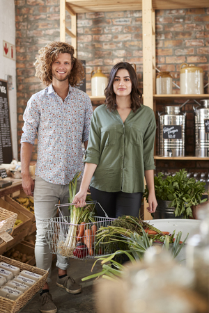 Portrait Of Couple Buying Fresh Fruit And Vegetables In Sustainable Plastic Free Grocery Store Фото со стока - 122609508