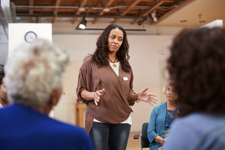 Woman Standing To Address Self Help Therapy Group Meeting In Community Center Stock fotó