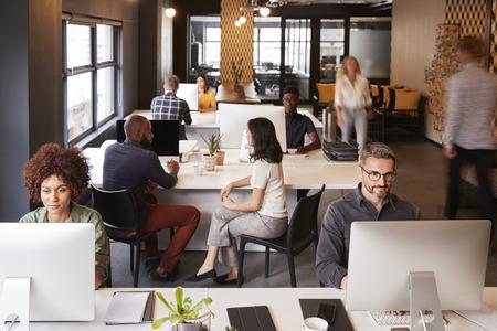 Verhoogde weergave van creatieve zakencollega's die in een druk kantoor werken Stockfoto