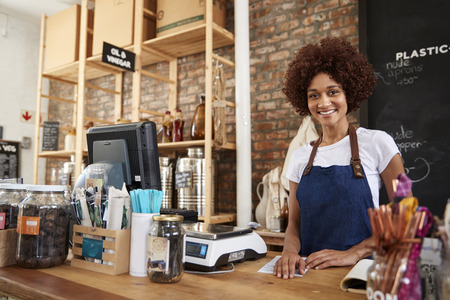 Portrait Of Female Owner Of Sustainable Plastic Free Grocery Store Behind Sales Desk Imagens