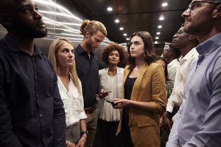 Des collègues de travail attendent ensemble dans un ascenseur de leur bureau