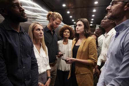 Work colleagues stand waiting together in an elevator at their office Imagens