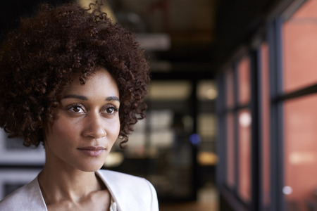 Millennial black businesswoman looking out of the window in an office, head and shoulders, close up