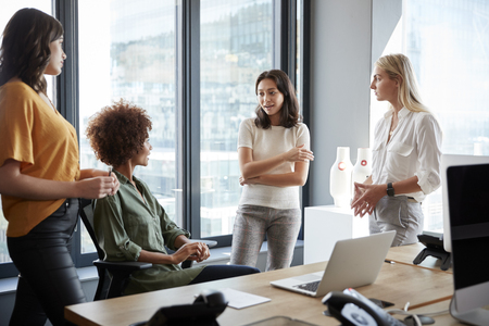 Four female colleagues in discussion at a desk in a creative office, three quarter length