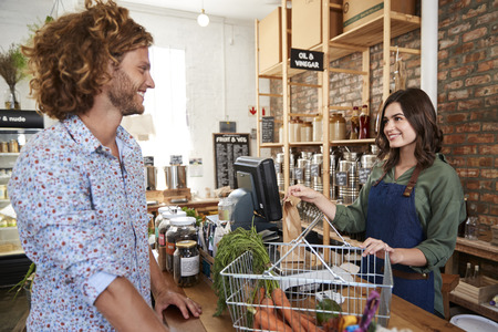 Customer Paying For Shopping At Checkout Of Sustainable Plastic Free Grocery Store Banque d'images - 122609866