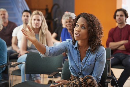 Frustrated Woman Asking Question At Group Neighborhood Meeting In Community Center