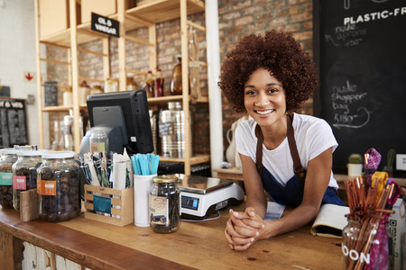 Portrait Of Female Owner Of Sustainable Plastic Free Grocery Store Behind Sales Desk Stock Photo