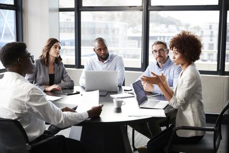 기업 비즈니스 회의에서 동료들에게 연설하는 밀레니엄 흑인 여성 사업가