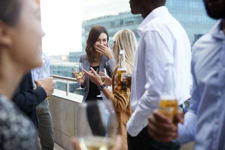 Compañeros de oficina socializando con bebidas en un balcón en la ciudad después del trabajo