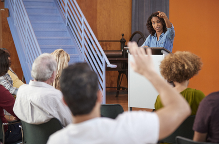 Woman At Podium Chairing Neighborhood Meeting In Community Centre Imagens