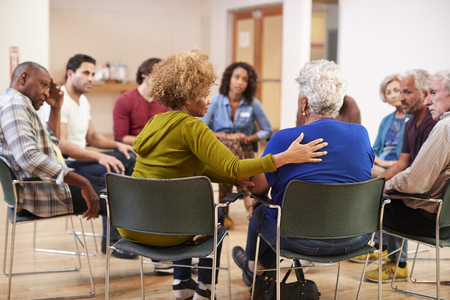 People Attending Self Help Therapy Group Meeting In Community Center Archivio Fotografico