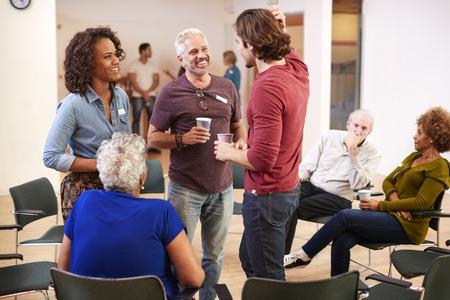 Grupo de personas socializando después de reunirse en el centro comunitario Foto de archivo