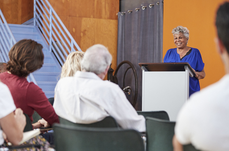 Senior Woman At Podium Chairing Neighborhood Meeting In Community Centre
